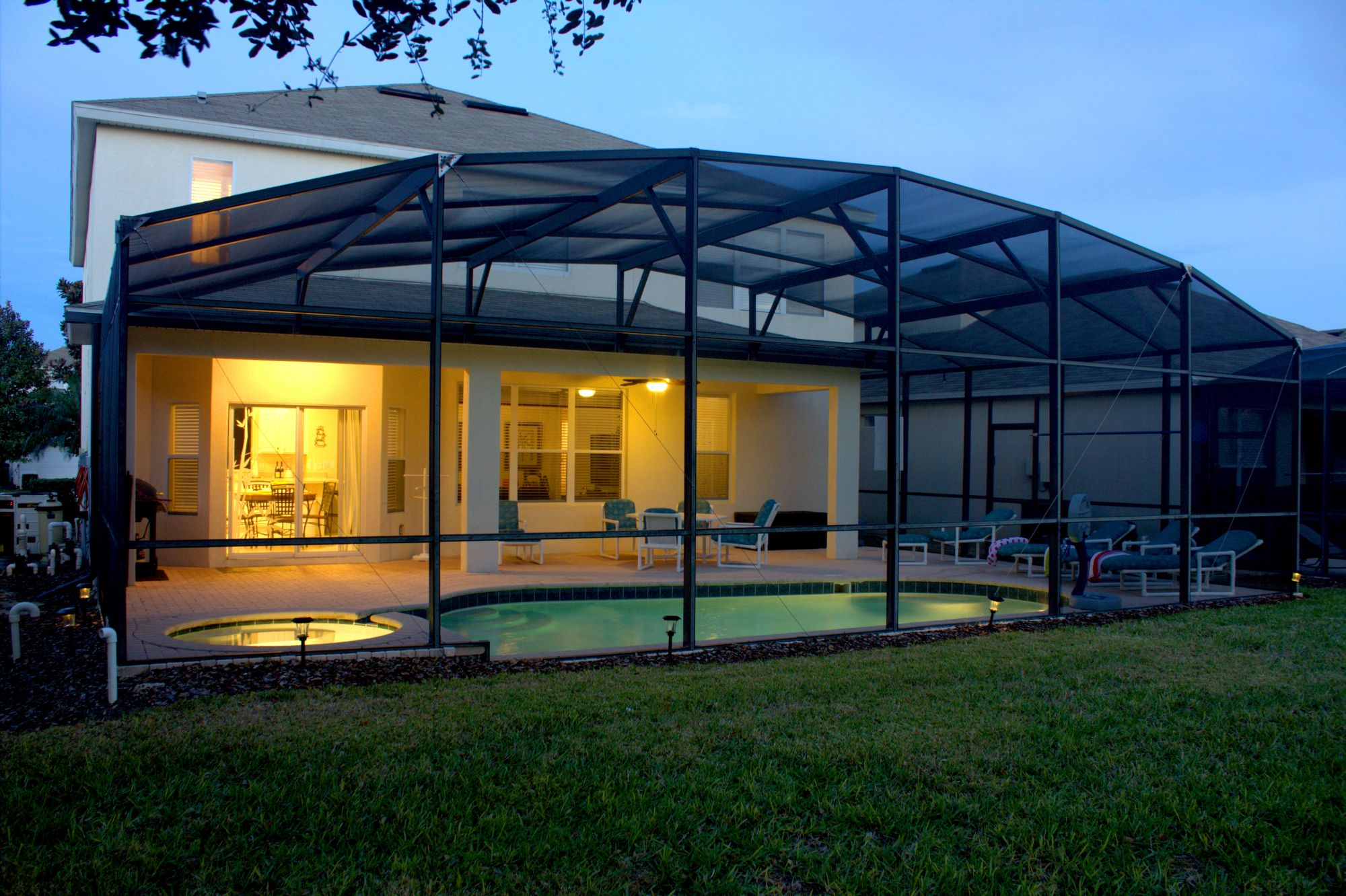 The Lit Screened In Pool And Spa Lanai And Back Of The